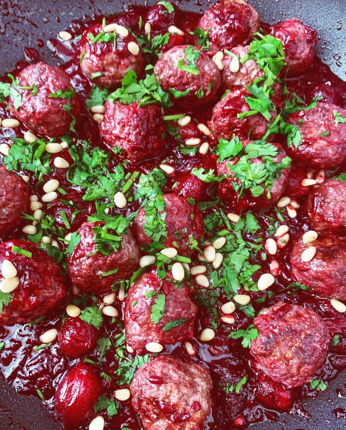 Meatballs in a ruby red cherry sauce from Aleppo, drizzled with coriander and pine nuts